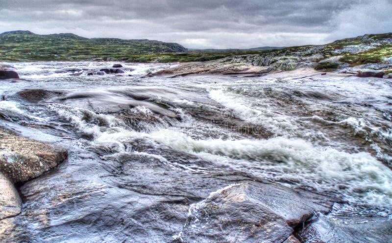 Rasender Fluss mitten in norwegischer Tundra stockbild