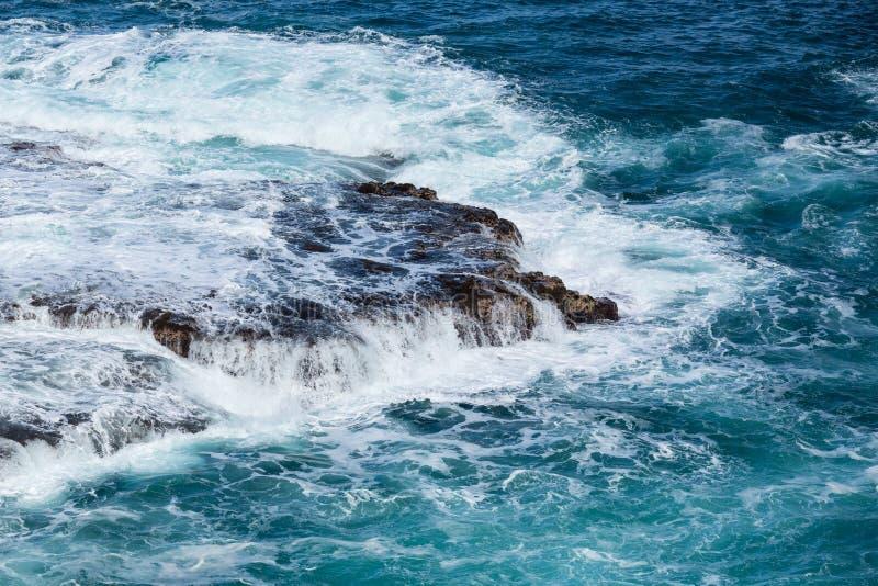 Rasendes Meer fließt über lave Felsen auf Uferzone lizenzfreie stockfotografie