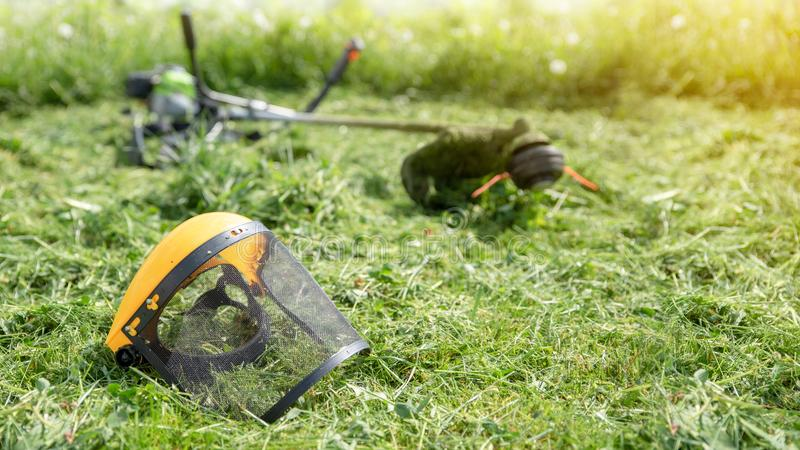 Rasentrimmer und schützende Gesichtsmaske auf gemähtem Gras, Sonnenlicht, Format der Fahne 16x9 lizenzfreie stockfotografie