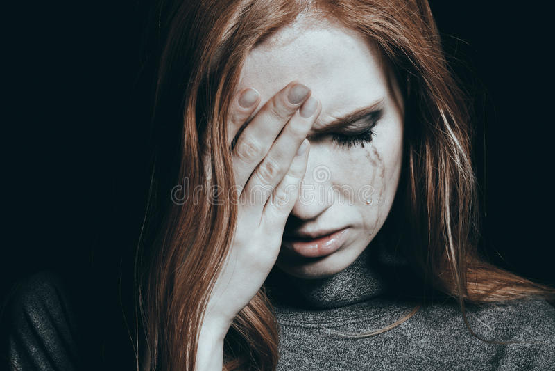Rasgones que caen abajo mejilla del ` s de la muchacha foto de archivo