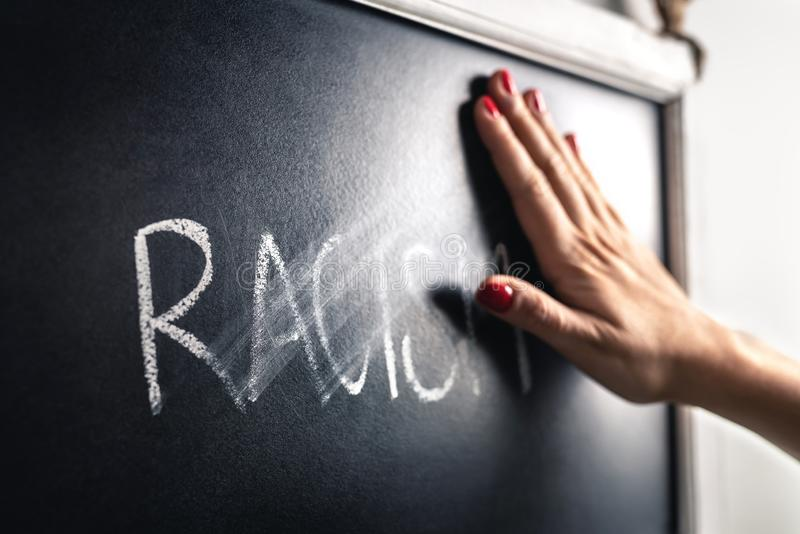 Rasismbegrepp Stoppa hat och diskriminering Mot fördom och våld Hand som av torkar och raderar ordet royaltyfri bild
