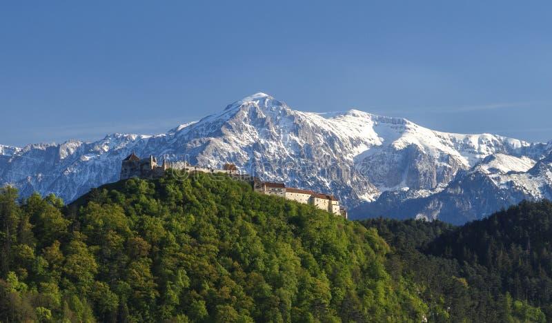 Rasnov城堡、历史的纪念碑和地标反对高山在日落点燃 免版税库存图片