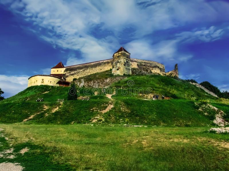 Rasnov Citadel on the hill against the blue sky and green grass. Medieval Transylvanian Fortress is a historic monument and stock photography