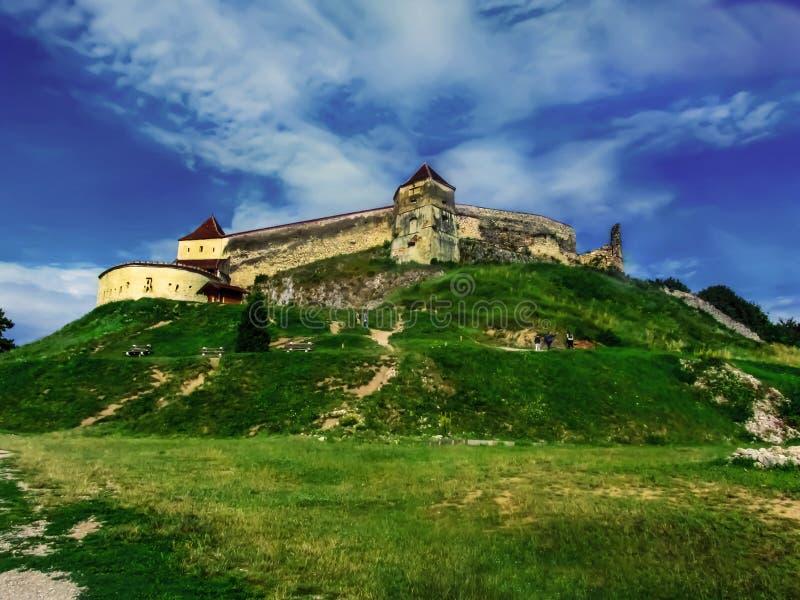 Rasnov Citadel sulla collina contro il cielo blu e l'erba verde La fortezza medievale della Transilvania è un monumento storico e fotografia stock