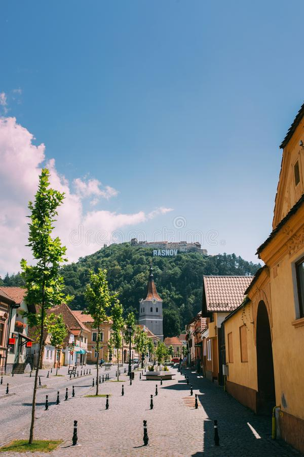 RASNOV, ROMANIA - AUGUST 1, 2017: Main street of ancient Saxon town on bright sunny day. Fortified church and medieval castle on. The hill stock photography