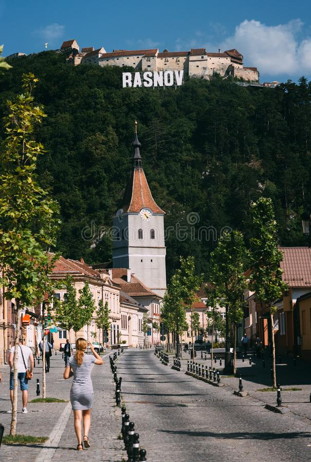 RASNOV, ROMANIA - AUGUST 1, 2017: Main street of ancient Saxon town on bright sunny day. Fortified church and medieval castle on. The hill royalty free stock photos