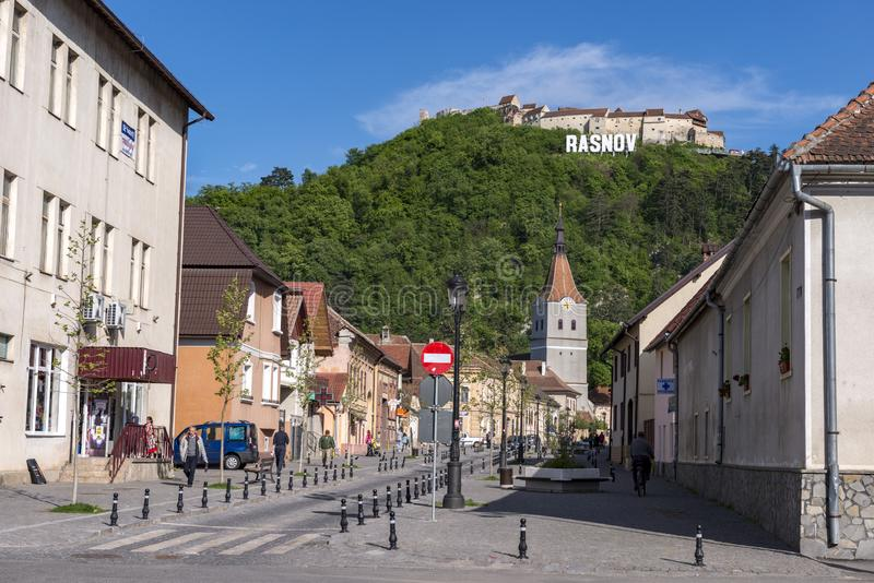 Rasnov, Romania - May, 2017: View of the Rasnov city mainstreet (Brasov county (Romania), with the hill of the medieval Rasnov. Fortress and city name in the stock image