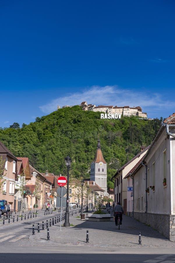 Rasnov Rumänien - Maj, 2017: Sikt av den Rasnov stadsmainstreeten (det Brasov länet (Rumänien), med kullen av den medeltida Rasno royaltyfria bilder