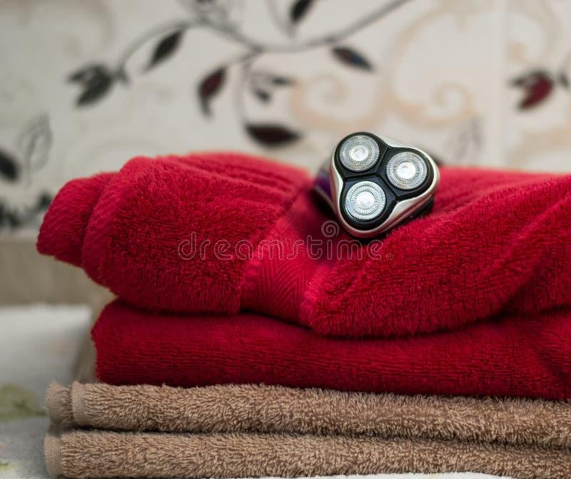 Rasoir rotatoire bleu électrique avec trois lames près des serviettes noires de cas et de bain photo stock