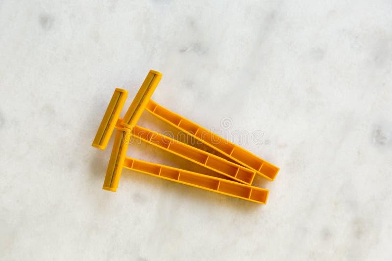 Rasoirs en plastique jetables sur la table d'albâtre photo stock