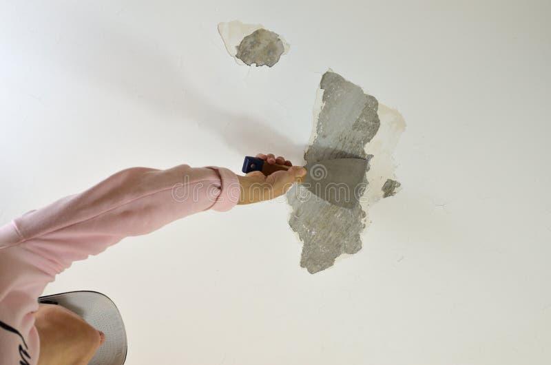 Raspando um teto com uma ferramenta foto de stock