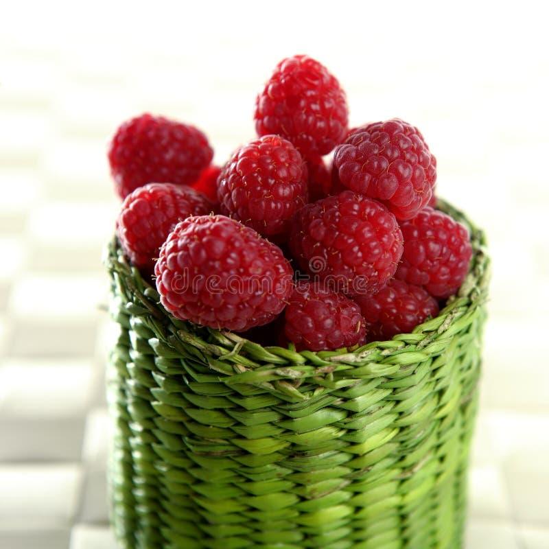 Raspberries. A group of fresh raspberries in a green little basket royalty free stock photo