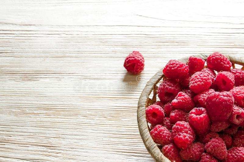 Raspberries in a basket on a light wooden background royalty free stock images