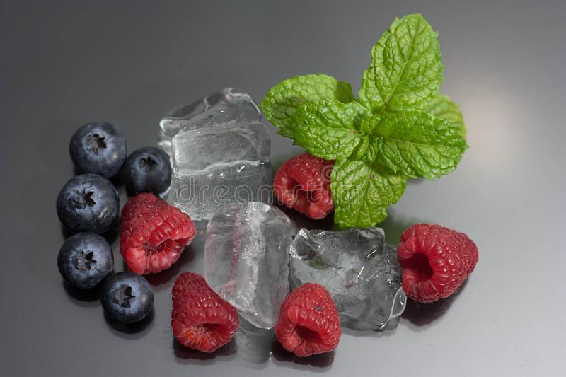 Raspberries and blueberries on black background stock images