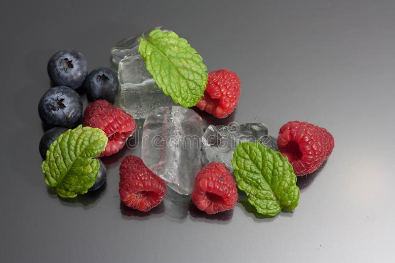 Raspberries and blueberries on black background royalty free stock image