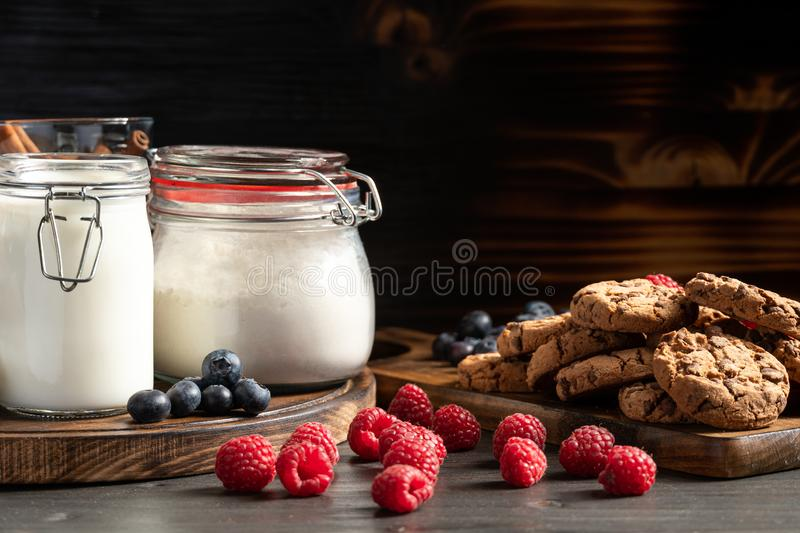Raspberries, blueberries and homemade cookies placed on wooden platters royalty free stock images