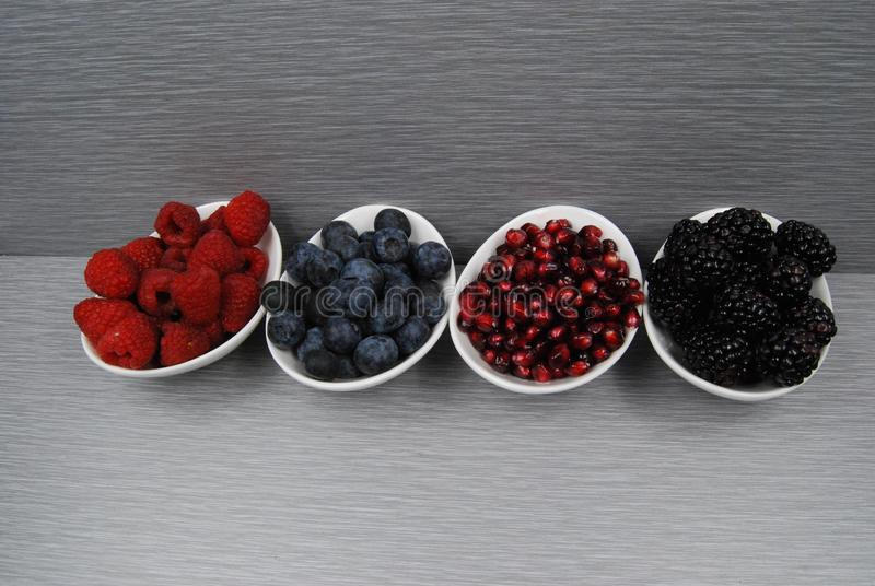 Fresh Berries in white dishes on a grey background. Raspberries, blueberries, pomegranate, blackberries, Healthy and high in anti-oxidants. Vibrant reds and stock photos