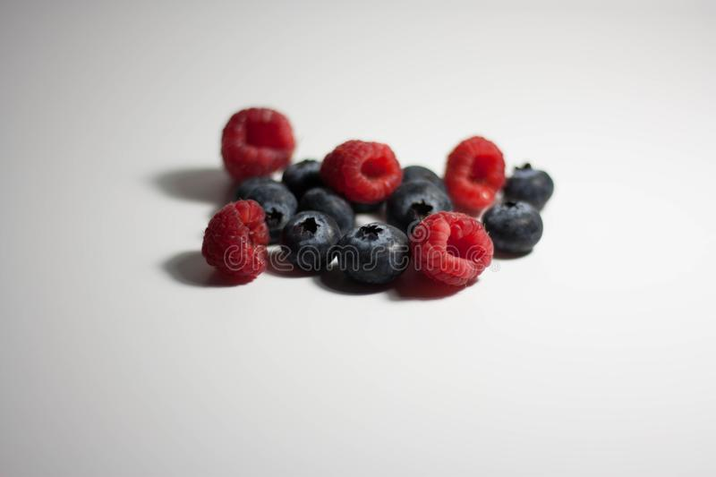 Raspberries and blueberries on white background stock images