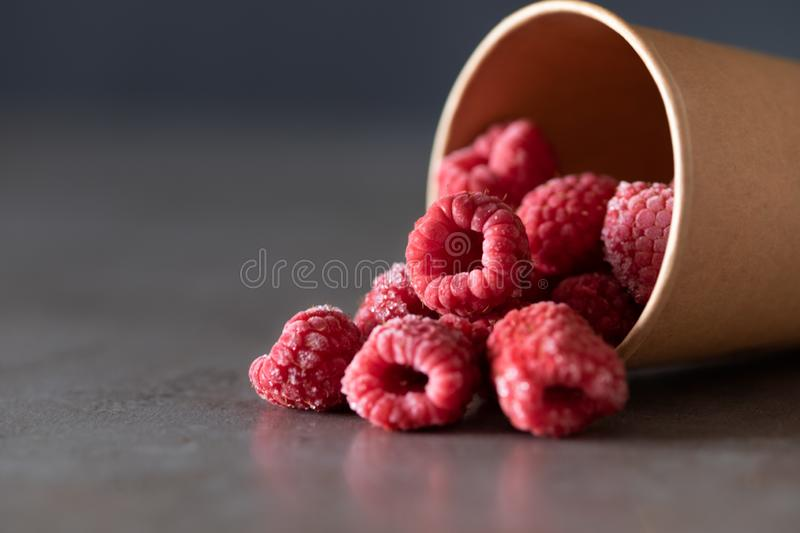 Raspberries in the cup on gray background. Frozen raspberries in the disposable cup on gray background. Place for text royalty free stock photo