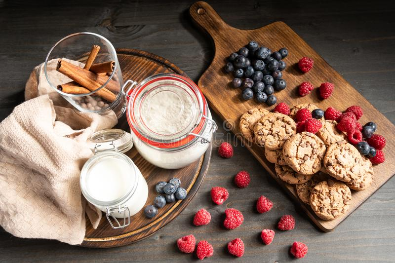 Raspberries, homemade cookies and milk on wooden support, top view royalty free stock photos