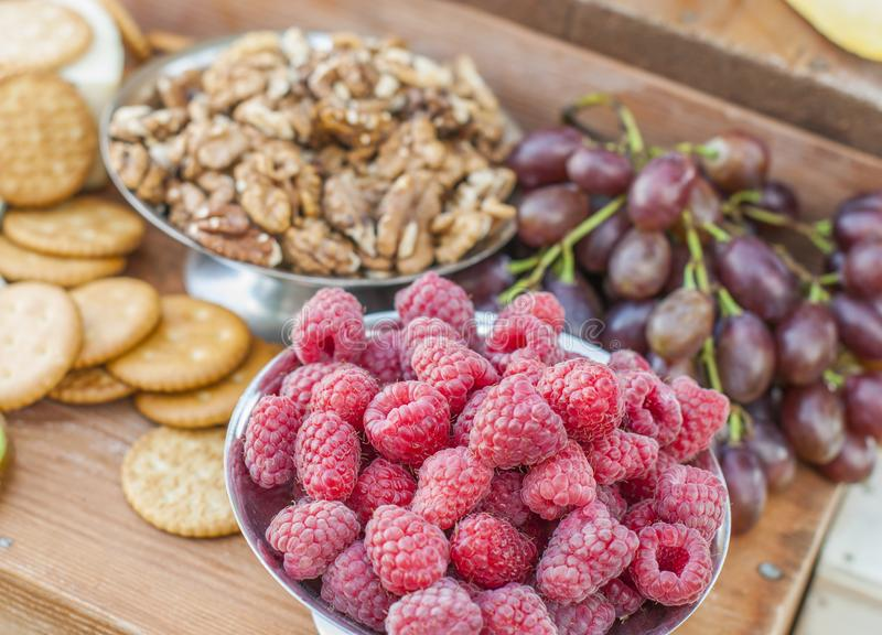 Raspberries and nuts on a beautifully vintage decorated table. Outdoor wedding reception royalty free stock photography