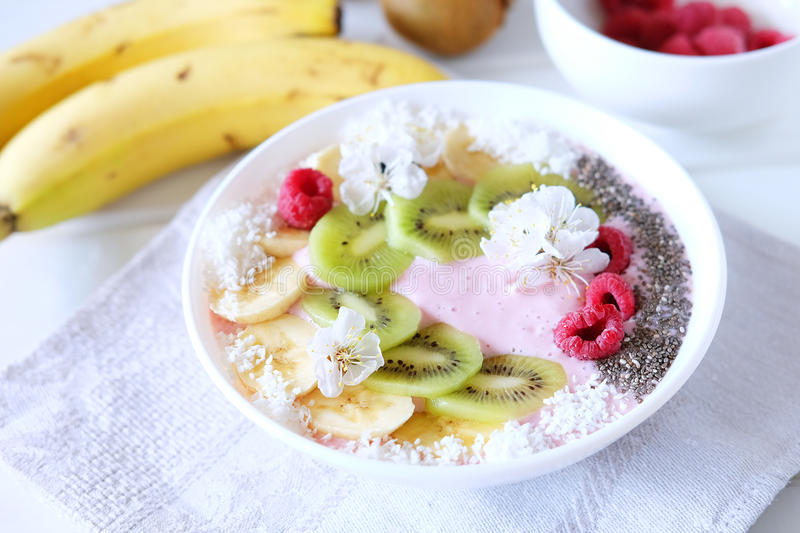 Raspberry and banana smoothie bowl with kiwi slices, shredded co. Conut and chia seeds. Healthy food concept royalty free stock image