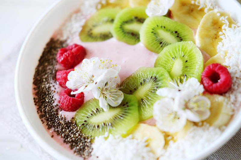 Raspberry and banana smoothie bowl with kiwi slices, shredded co. Conut and chia seeds. Healthy food concept royalty free stock photography