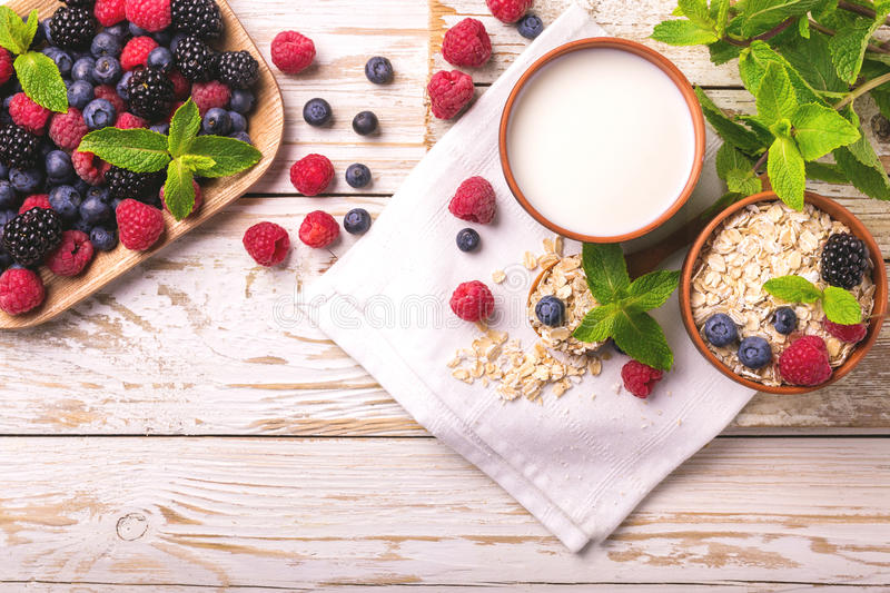 Raspberry, blackberry and blueberry, oatmeal breakfast with milk royalty free stock photos
