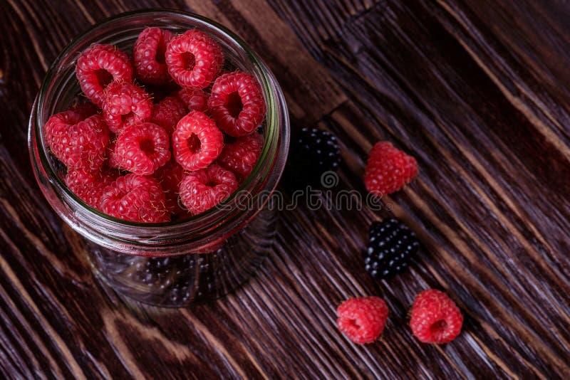 Raspberry and blackberry sweet organic juicy berries in single glass jar on dark wooden table stock photos