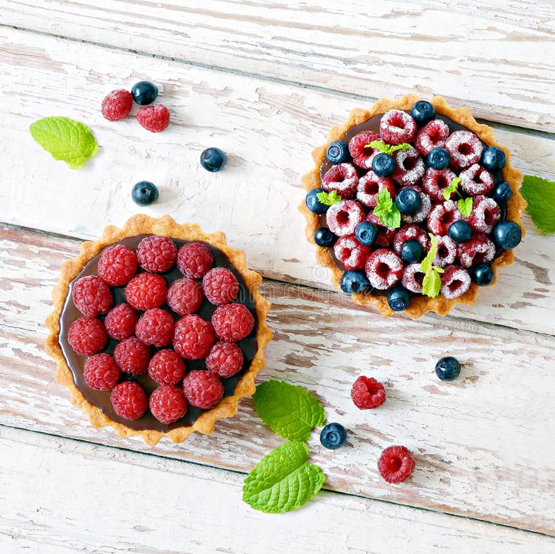 Raspberry and blueberry tartlets with chocolate ganache, fresh berries and mint leaves, selective focus. Fresh fruit tart stock photos