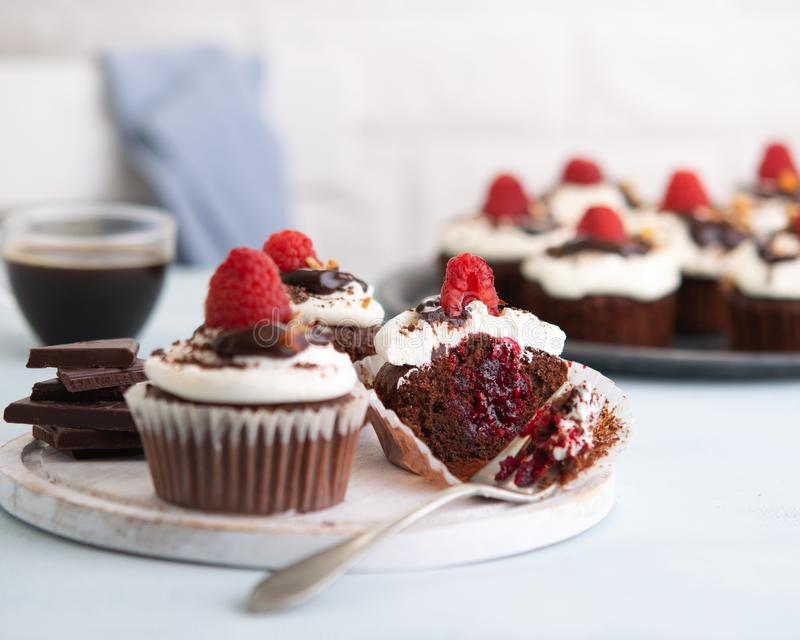 Raspberry chocolate cupcakes with cupcake cut in half jam filling cup of coffee and fresh raspberries on the table, light royalty free stock images