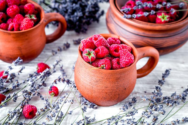 Raspberry composition in pottery with dry lavender rustic backgr. Raspberry composition in pottery pots and cups and with dry lavender bouquet on rustic desk stock image