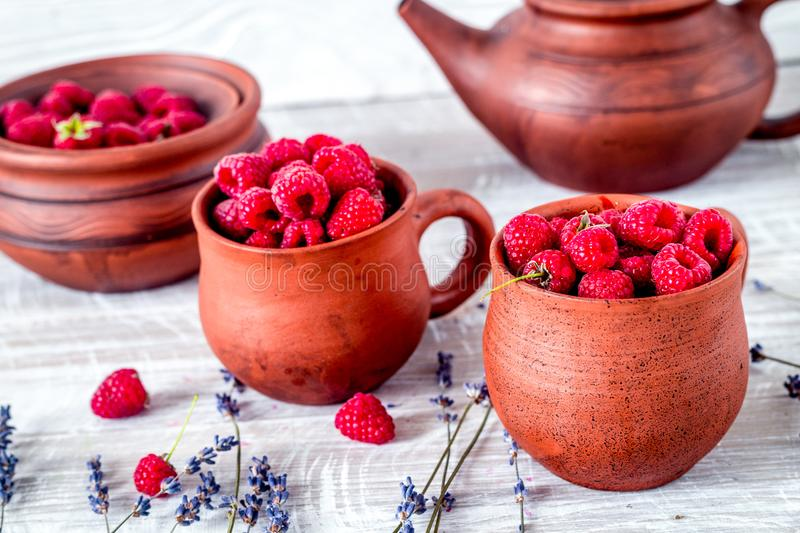 Raspberry composition in pottery with dry lavender rustic backgr. Raspberry composition in pottery pots and cups and with dry lavender bouquet on rustic desk stock photos