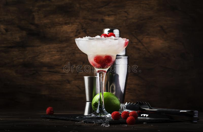 Raspberry daiquiri, alcoholic cocktail with white rum, lime juice, raspberries and crushed ice in tall glass, on wooden bar. Counter  with steel bar tools royalty free stock photos