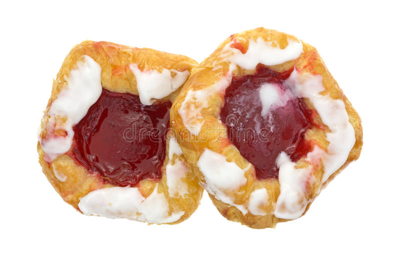 Raspberry danish pastries on a white background top view. Top view of two freshly baked raspberry filled danish pastries isolated on a white background royalty free stock photo