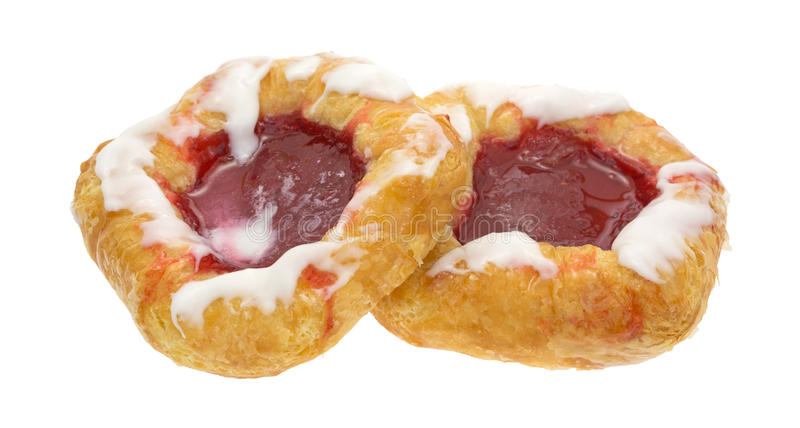 Raspberry danish pastries on a white background. Two freshly baked raspberry filled danish pastries isolated on a white background royalty free stock photography