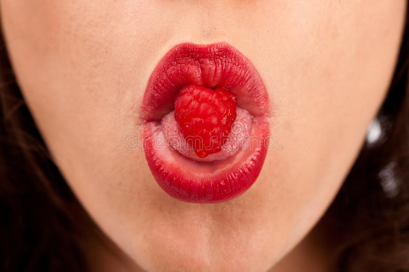 Raspberry heart. Fresh and attractive raspberry with a shape of the heart in a women's mouth stock photos