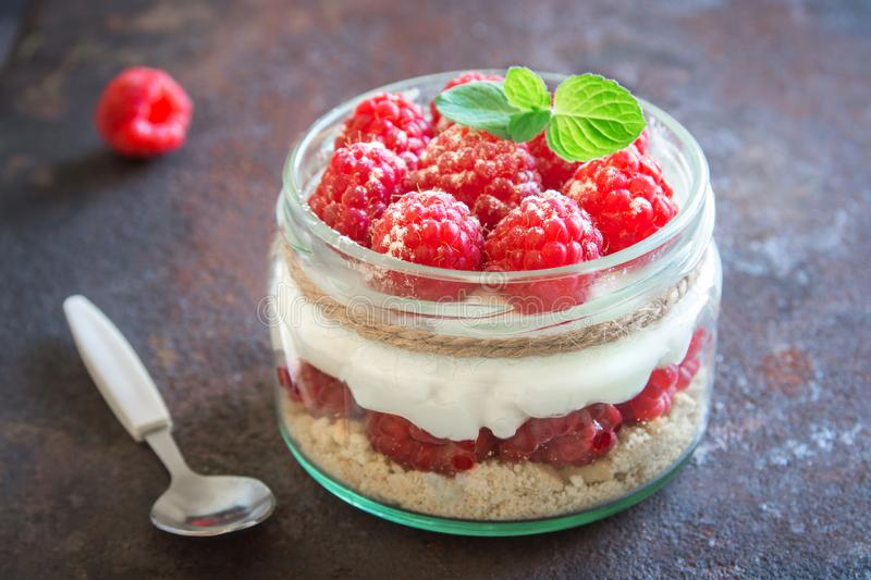 Raspberry layered dessert. Cheesecake in glass jar with fresh raspberries and cream cheese. Healthy homemade summer berry dessert royalty free stock images