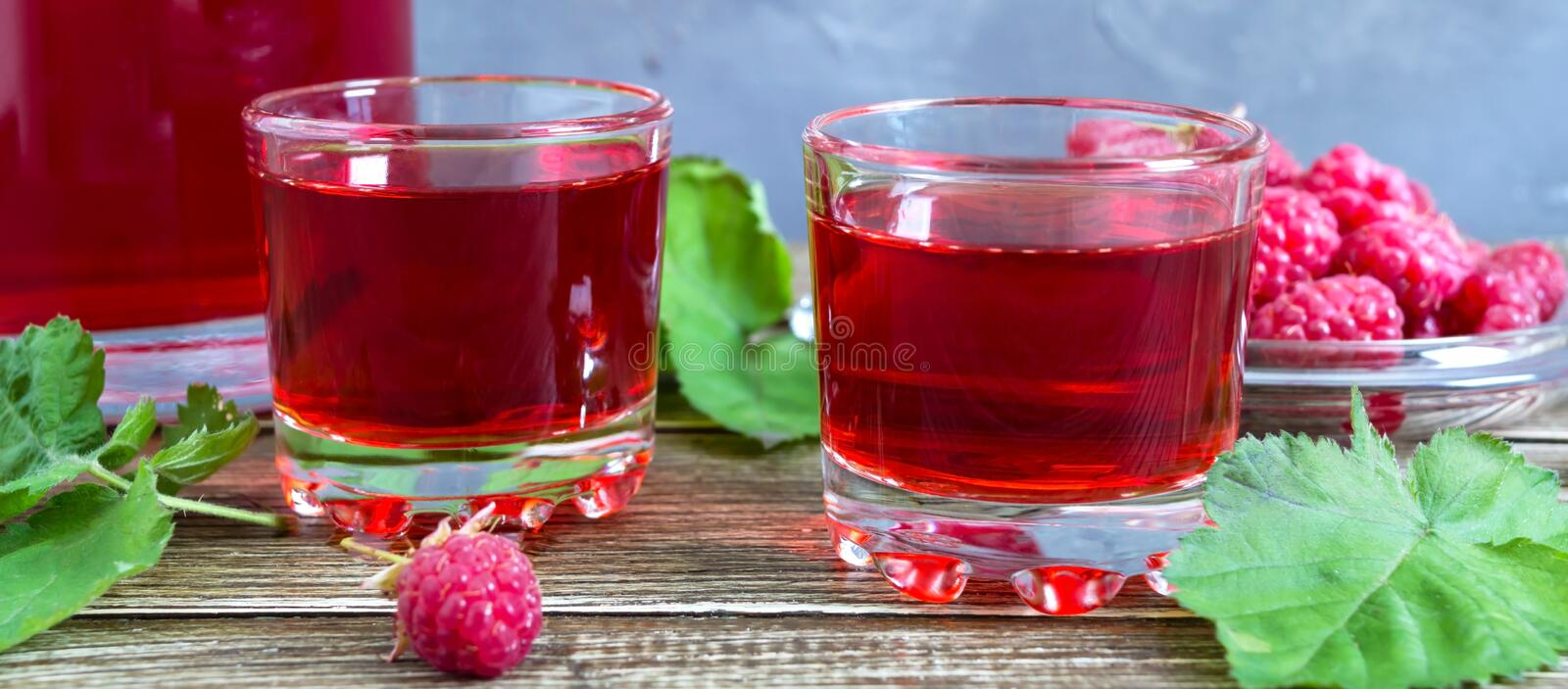 Raspberry liqueur in glass, fresh natural ripe organic berries and green leaves on a rustic wood background. Alcoholic flavored royalty free stock images
