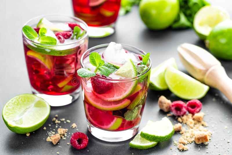 Raspberry mojito cocktail with lime, mint and ice, cold, iced refreshing drink or beverage closeup stock images