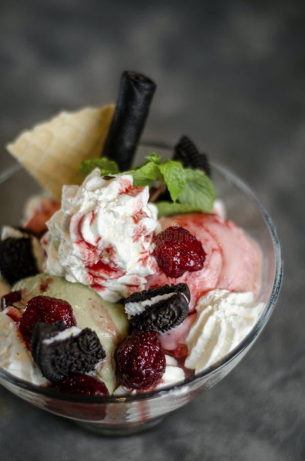 Raspberry and pistachio ice cream sundae dessert in bowl stock image