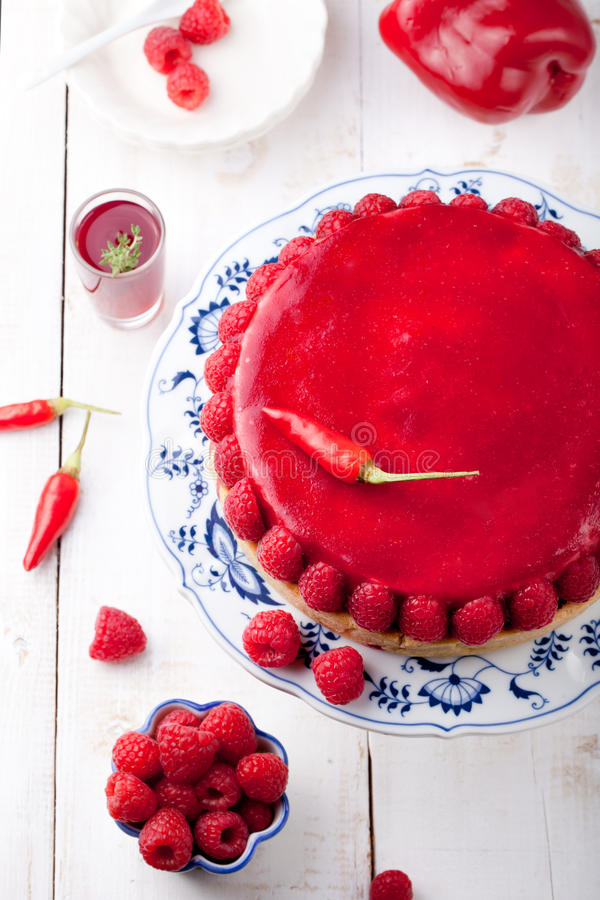 Raspberry and roast bell pepper mousse cake, cheesecake chili. Raspberry and roast bell pepper mousse cake, cheesecake with fresh chili pepper on a white wooden royalty free stock images