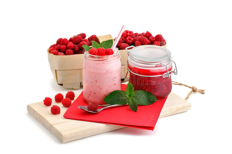 Raspberry smoothies, raspberry jam and a basket with ripe raspberries on a white background. An isolated object royalty free stock images