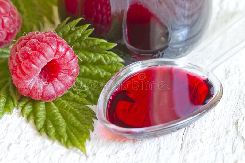 Raspberry syrup on spoon alternative medicine stock image