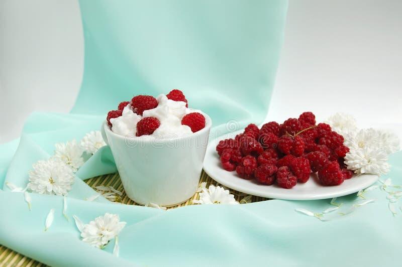 Raspberrys com creme chicoteado branco fotografia de stock royalty free