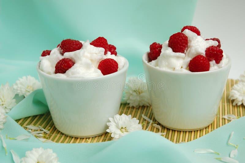 Raspberrys mit weißer gepeitschter Sahne lizenzfreies stockbild