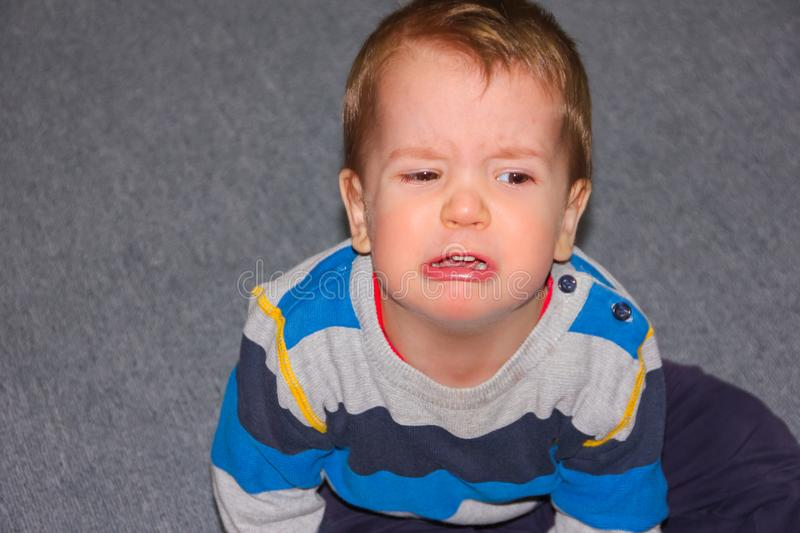 A rasped and hurt child sits on the floor. The little boy pouted stock photos