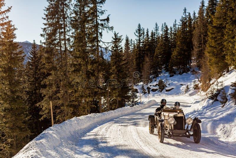 Rassemblement classique d'entraînement de voiture de course de vintage sur la route de couvert de neige photographie stock libre de droits