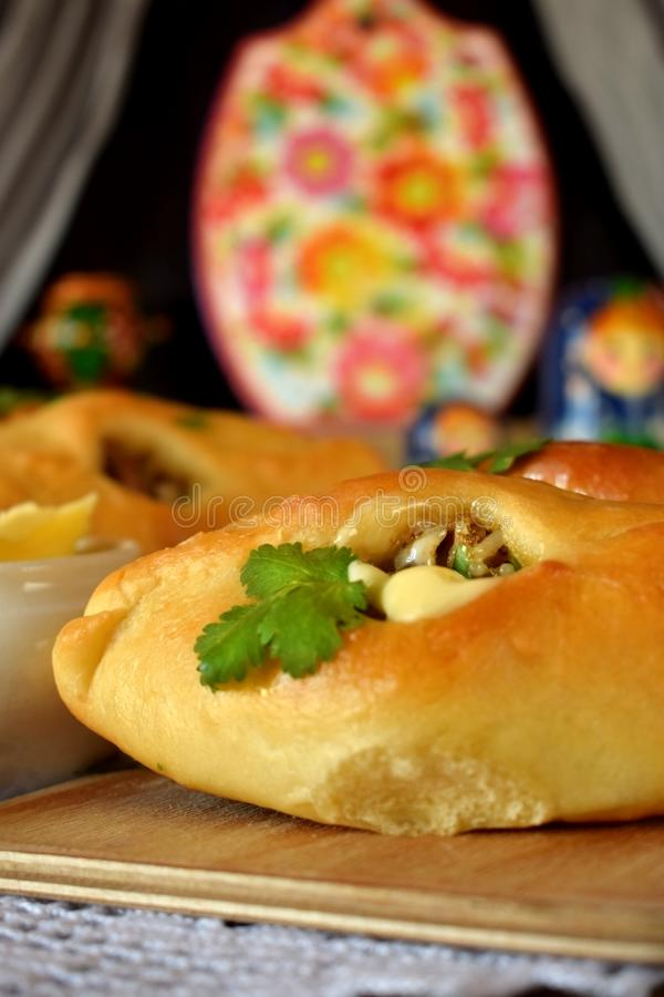 Rasstegai pie with fish filling. Traditional meal of Russian cuisine. Russian dolls in the background stock photo