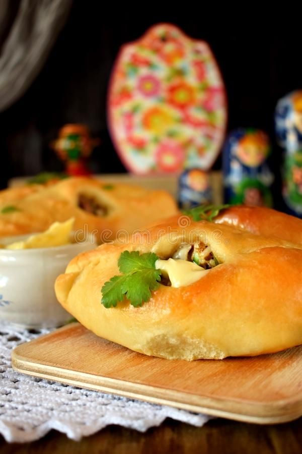 Rasstegai pie with fish filling. Traditional meal of Russian cuisine. Russian dolls in the background royalty free stock images